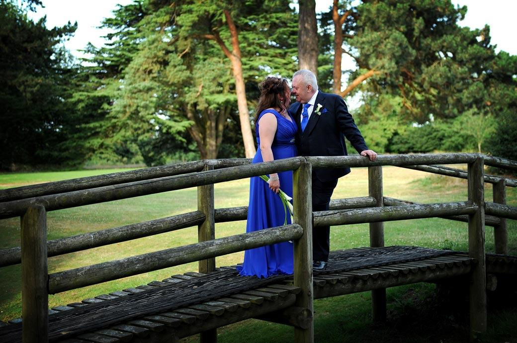 Newlywed couple standing having an intimate conversation together on a wooden bridge captured in this wedding photograph taken at relaxing Surrey wedding venue Coulsdon Manor