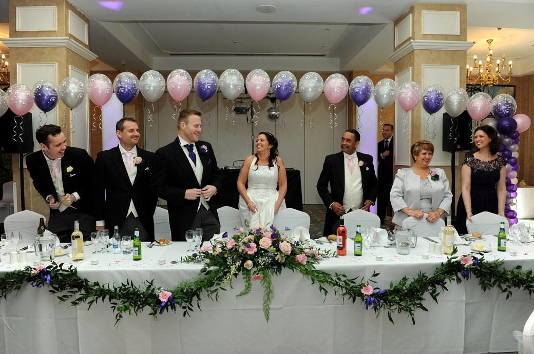 All smiles as the Bride and Groom arrive at the head table for the wedding breakfast captured by Surrey Lane wedding photographers at Coulsdon Manor in The Manor House Suite