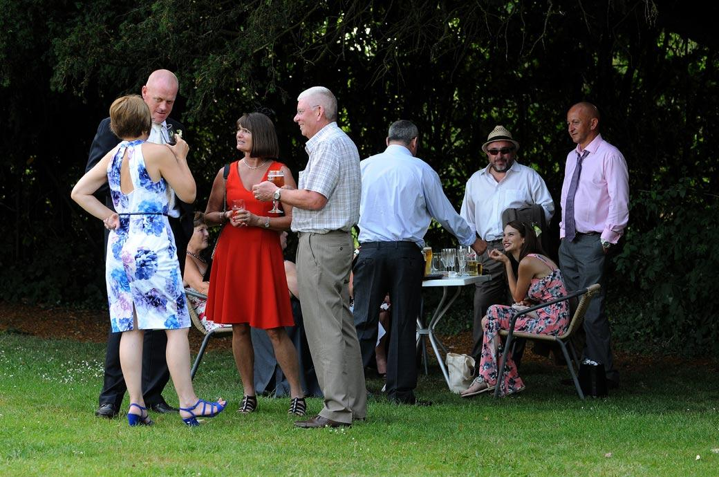 Guests relaxing and chatting with a drink in the shade on a hot summers day in this wedding picture taken at Surrey wedding venue Coulsdon Manor out on the back lawn