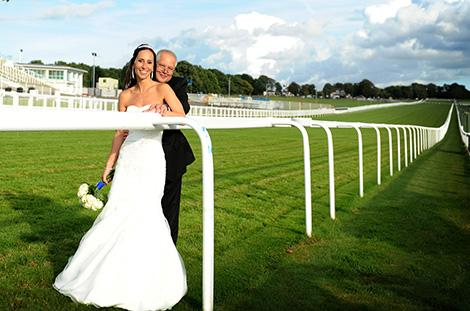 Happy wedding photograph of a smiling Bride and Groom after getting married at the Epsom Downs Racecourse Surrey wedding venue and now strolling along the grassy track