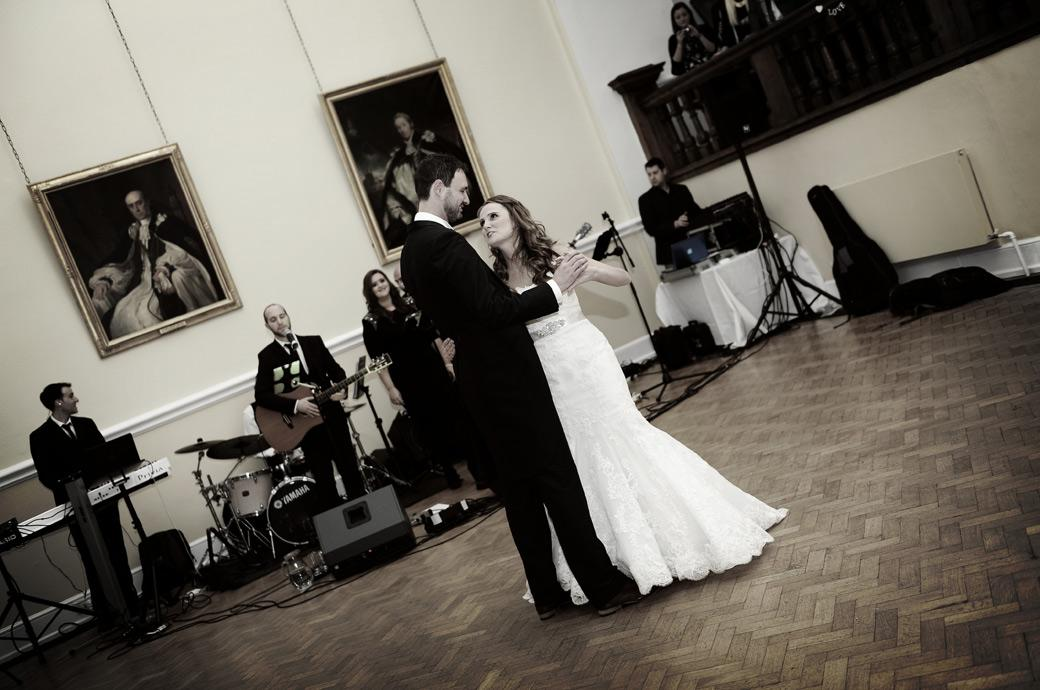 The couple get into their stride as the band liven up in this wedding picture taken during the first dance by Surrey Lane wedding photography in Farnham Castle's Great Hall