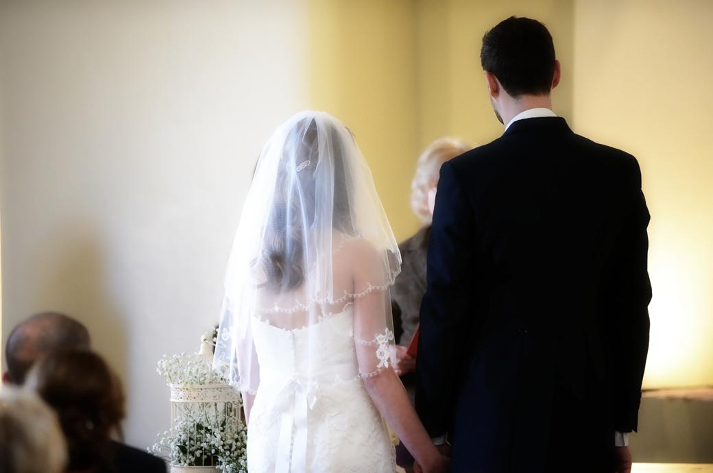 The Bride and Groom stand before the Registrar in this wedding picture taken as they are pronounced husband and wife in The Lantern Hall at Farnham Castle Surrey