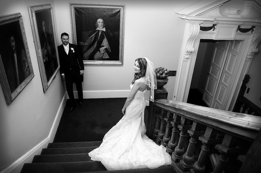 The Bride looks over her shoulder at her Surrey Lane wedding photographers in this wedding picture taken as her husband waits for her in Farnham Castle in The Bishop's Palace