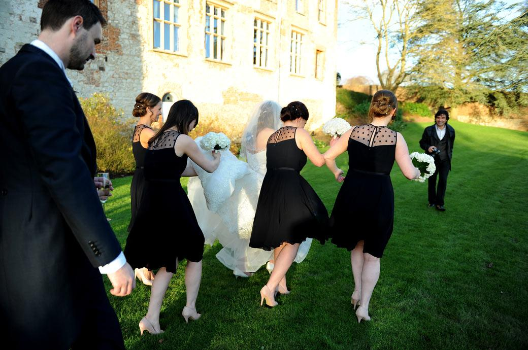 Bridesmaids and Bride with dress aloft negotiate their sinking heels in The Great Lawn in this light-hearted wedding photo taken outside Farnham Castle in Surrey