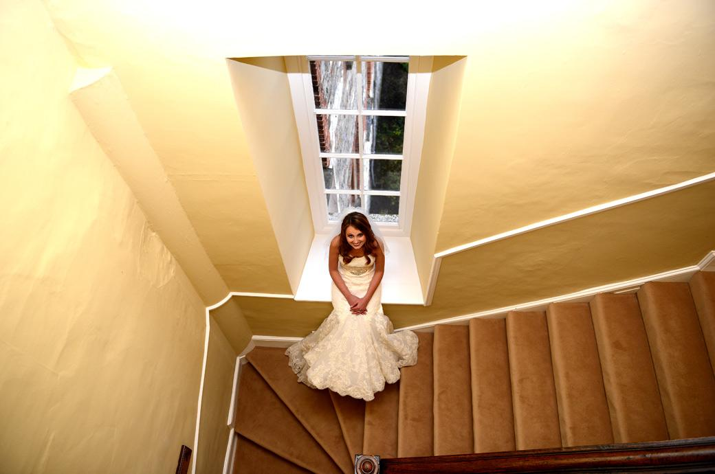 Bride sitting in an empty window sill in a hallway looking up smiling at her Surrey Lane wedding photographer in this fun wedding photograph taken at Farnham Castle