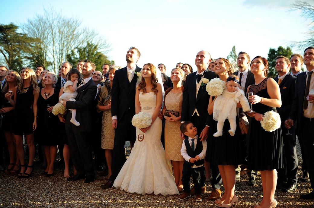 Newly-weds with their family and guests looking up at the Surrey Lane wedding photographer in this relaxed wedding picture taken from the ground at Farnham Castle in Surrey