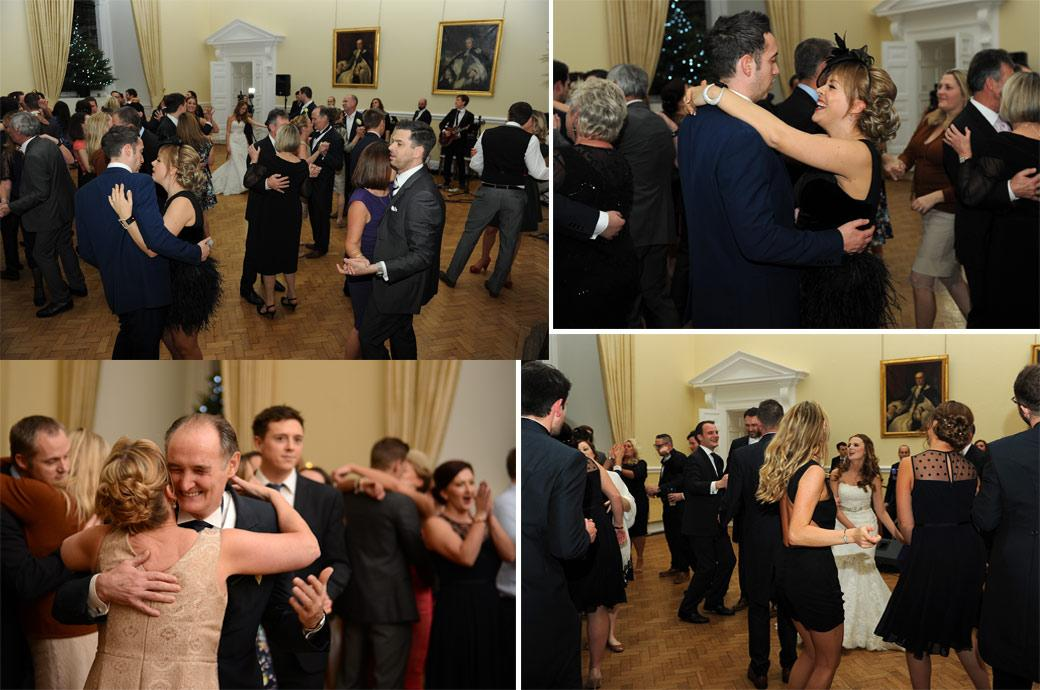 Everyone takes to the floor whilst the band plays in these informal dancing wedding photos taken in The Great Hall at Farnham Castle by Surrey Lane wedding photographers