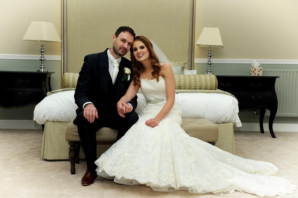 Newly-weds pose together in this wedding picture taken as they sit before the bed in their grand wedding suite in the luxurious and ancient Surrey wedding venue Farnham Castle