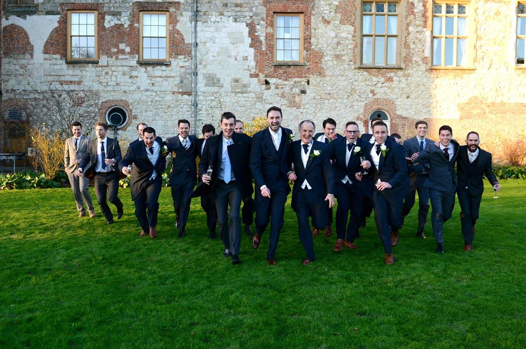 The gents have fun running towards the Surrey Lane wedding photographers in this special requested wedding photograph on The Great Lawn outside Farnham Castle Surrey