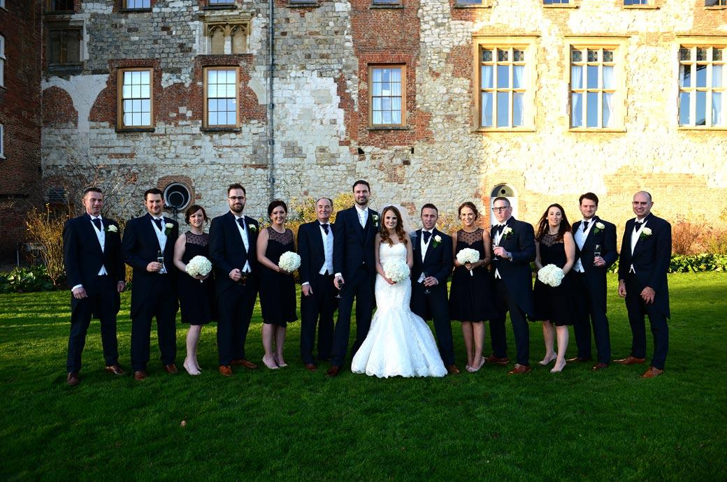 Bride and Groom with their Bridesmaids and Groomsmen in this relaxed group wedding photograph taken on The Great Lawn outside Farnham Castle a fine Surrey wedding venue