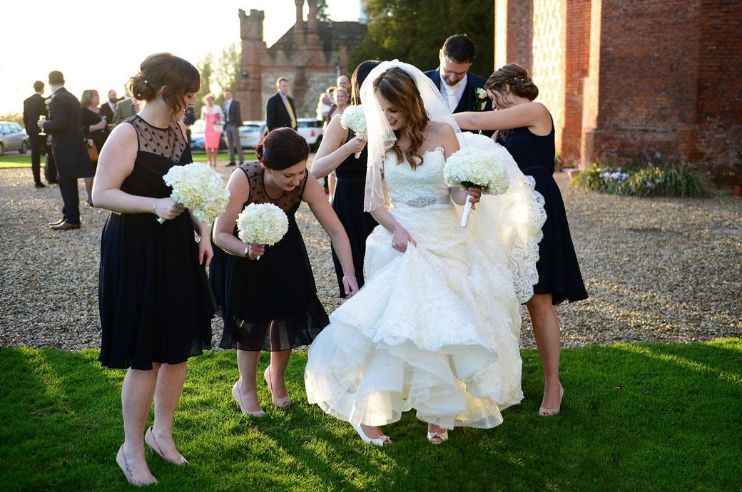 Groom and Bridesmaids in this wedding picture helping the Bride with her dress as she walks on The Great Lawn captured by Surrey Lane wedding photographers at Farnham Castle