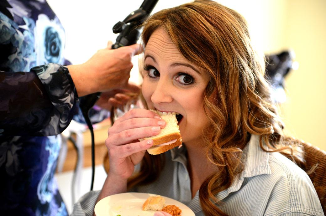A hungry Bride tucks into a sandwich during her hair dressing captured in this fun wedding photo by a Surrey Lane wedding photographer at Farnham Castle in The Gatehouse