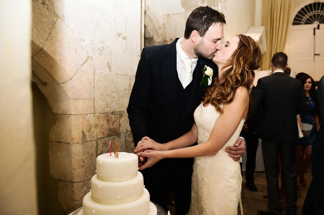 Bride and Groom's passionate kiss captured in this romantic wedding picture taken as they cut the wedding cake in The Stone Hall in Surrey at Farnham Castle