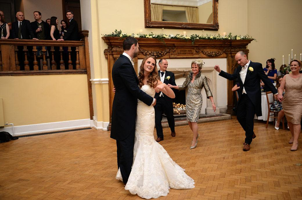 Parents join the married couple on the dancefloor is this lovely natural wedding photo taken in The Great Hall at Farnham Castle by Surrey Lane wedding photographers
