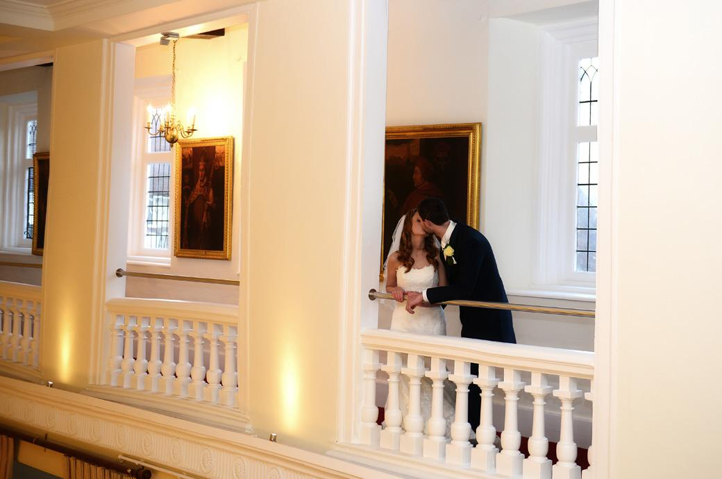 Bride and Groom have a kiss in this romantic wedding picture taken on the balcony at Surrey venue Farnham Castle overlooking the The Great Hall before dinner begins
