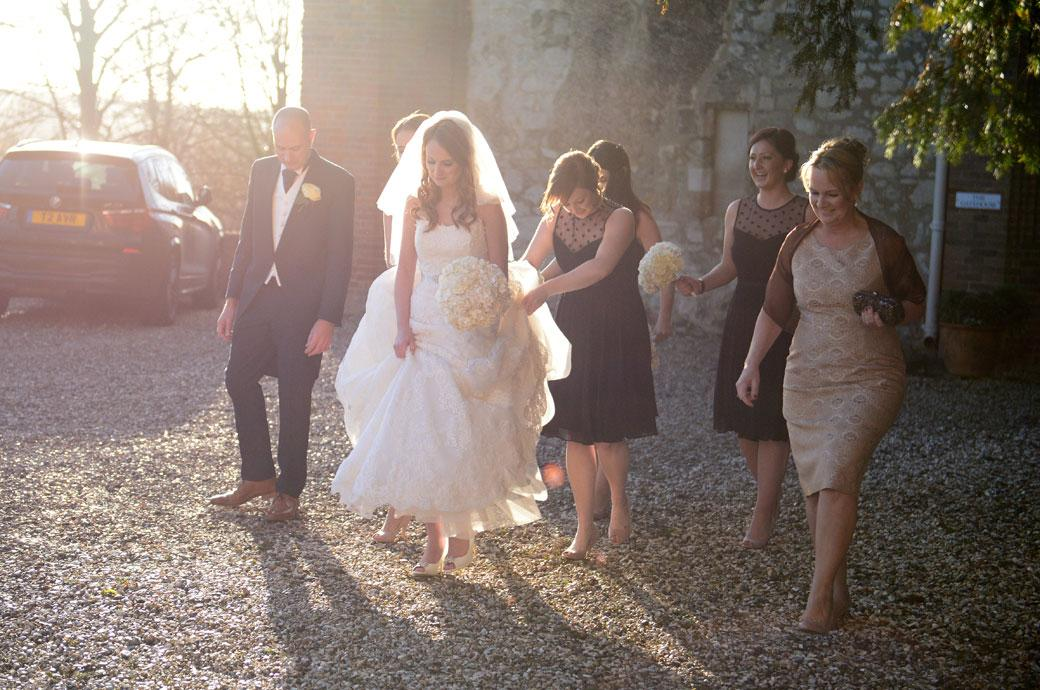Wedding photograph of a Bride walking cautiously over the shingle path from The Gatehouse towards the ceremony room at Farnham Castle by Surrey Lane wedding photographers