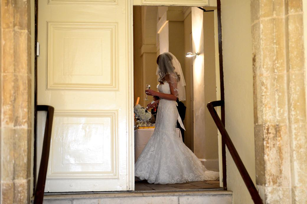 Wedding photograph of the Bride captured as she stands beyond the open main door champagne in hand at Surrey wedding venue Farnham Castle in The Stone Hall
