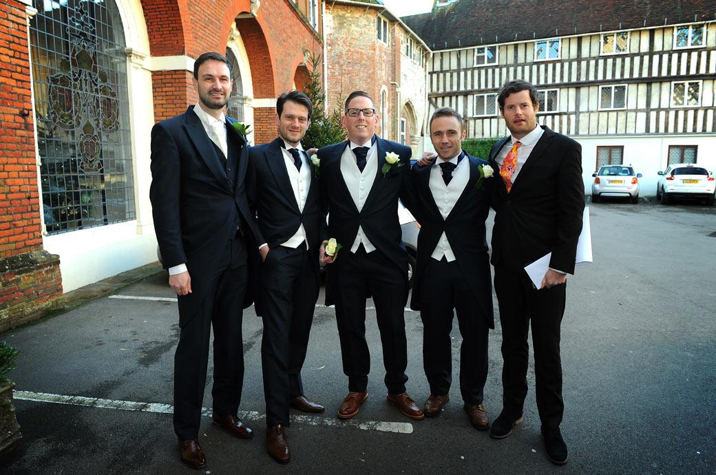 The Groom takes a moment from his duties for a quick pre wedding photo with his Groomsmen outside The Great Hall at the wonderful Surrey wedding venue Farnham Castle