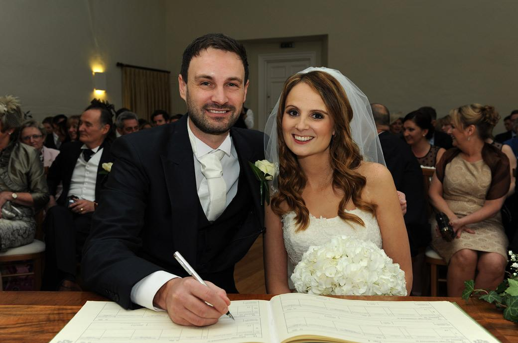 Happy smiling newly-weds pose in this sweet wedding photograph as the Groom signs the marriage register at Surrey wedding venue Farnham Castle in The Lantern Hall
