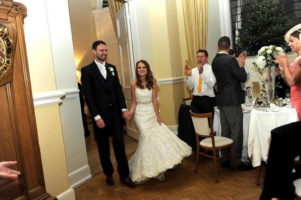 Beaming married couple enter The Great Hall for the wedding Breakfast to applause captured in this delightful wedding picture at Farnham Castle by Surrey Lane wedding photography
