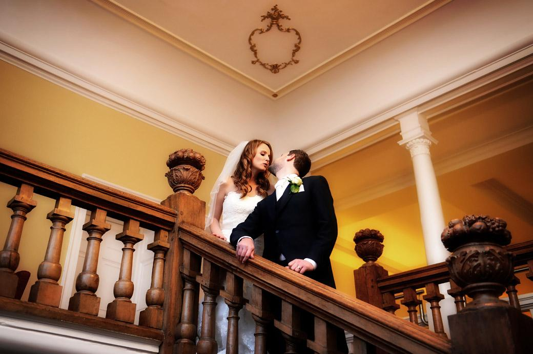 A moment between the Bride and Groom before they kiss captured in this wedding picture taken on the wooden staircase at Farnham Castle a magical Surrey wedding venue