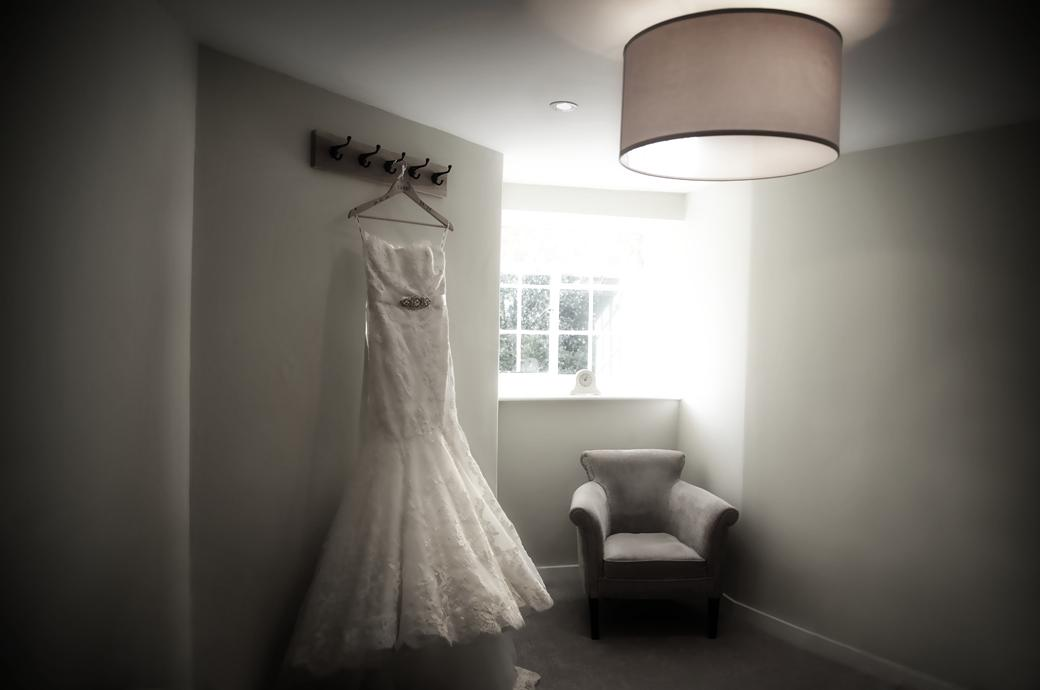 The Bride's beautiful dress hanging in one of the dressing rooms in The  Gatehouse in this wedding photograph taken in the ancient Surrey wedding venue Farnham Castle