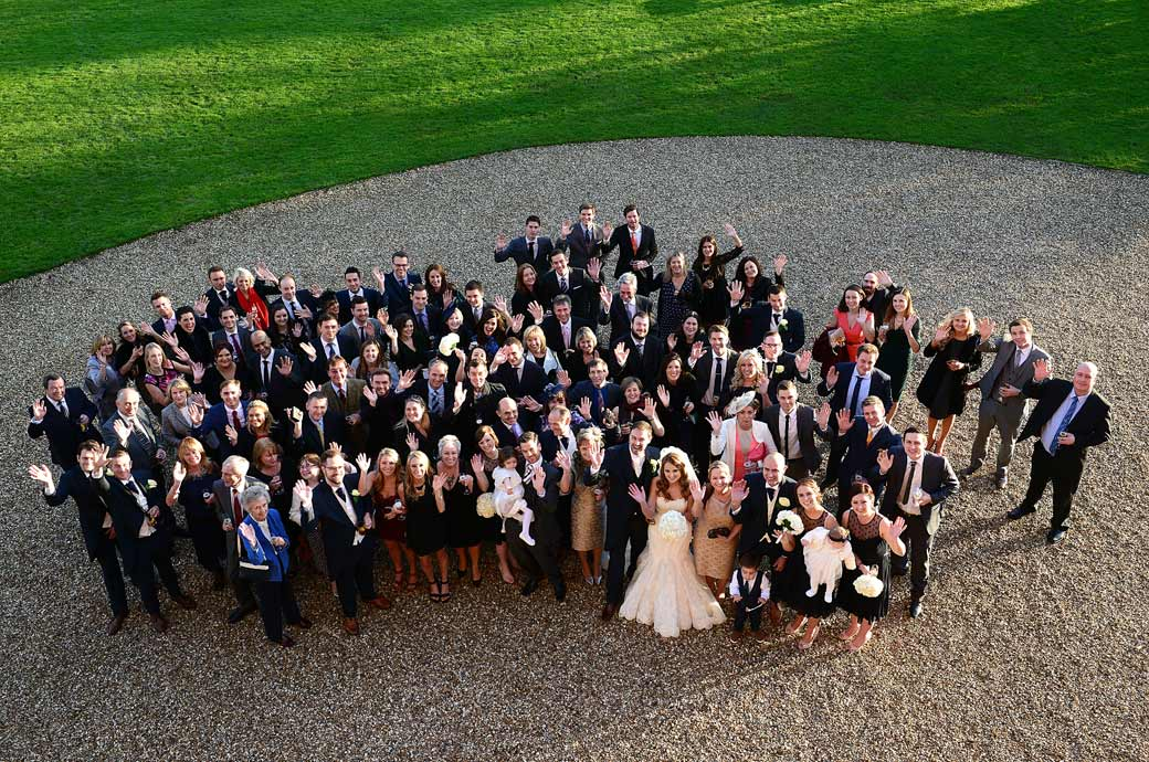 Everyone looking up to the wedding photographer on the second floor and waving in this fun group wedding photo captured at Surrey wedding venue Farnham Castle