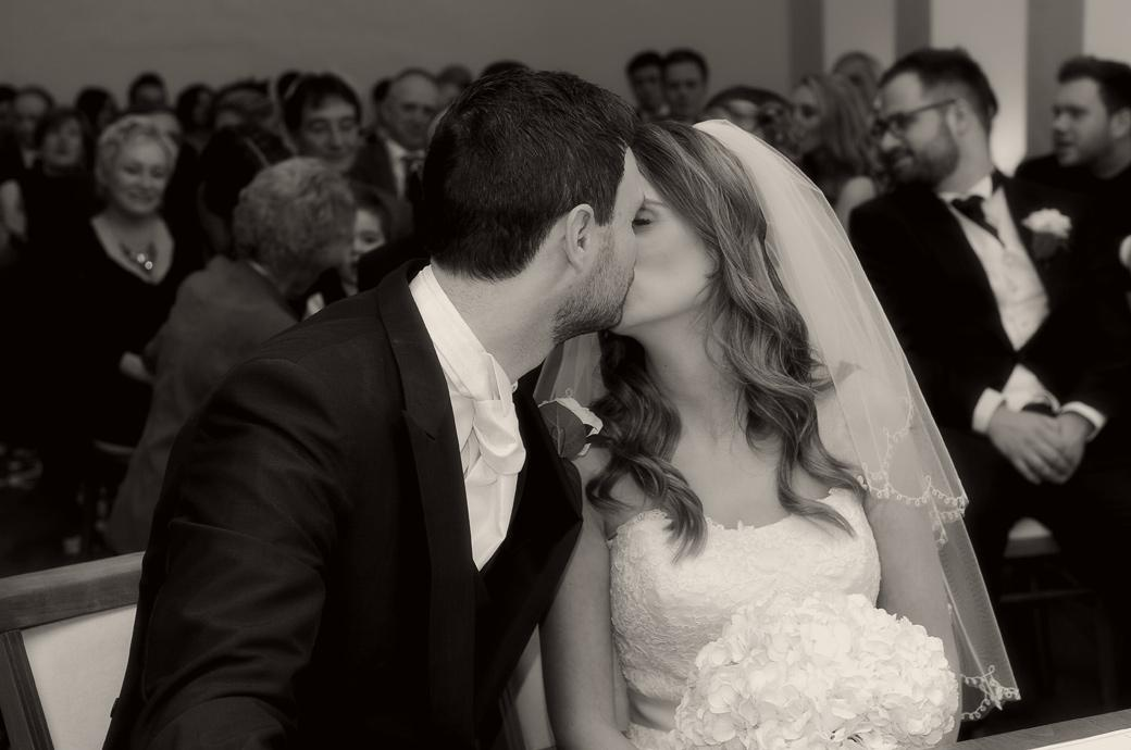 Newly-weds have a post register signing kiss captured in this romantic wedding picture taken by Surrey Lane wedding photography in The Lantern Hall at Farnham Castle