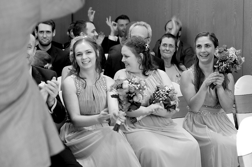 Laughter smiles and applause for the newlywed couple captured after the marriage ceremony at Surrey wedding venue Frensham Ponds Hotel Farnham