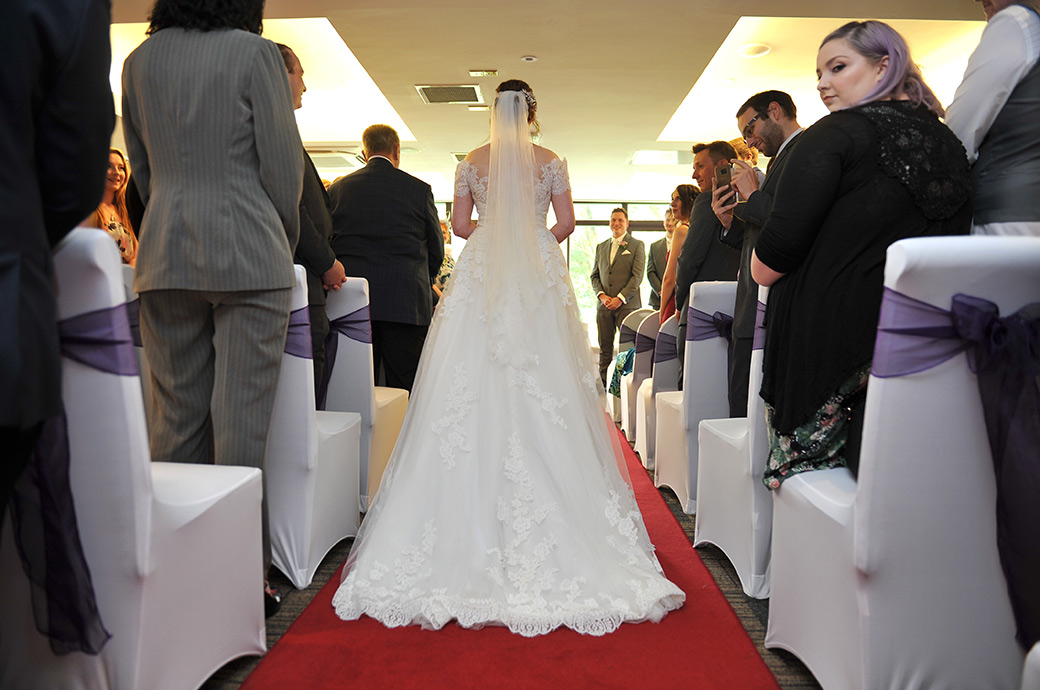 View from behind of the Bride at Surrey event venue Frensham Ponds Hotel walking down the wedding aisle at the start of the marriage ceremony