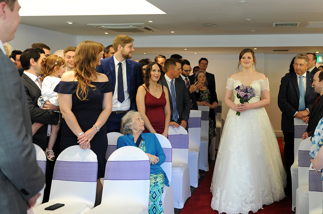 A beautiful Bride at  Surrey event venue Frensham Ponds Hotel catches the eyes of her Groom as she walks down the wedding aisle