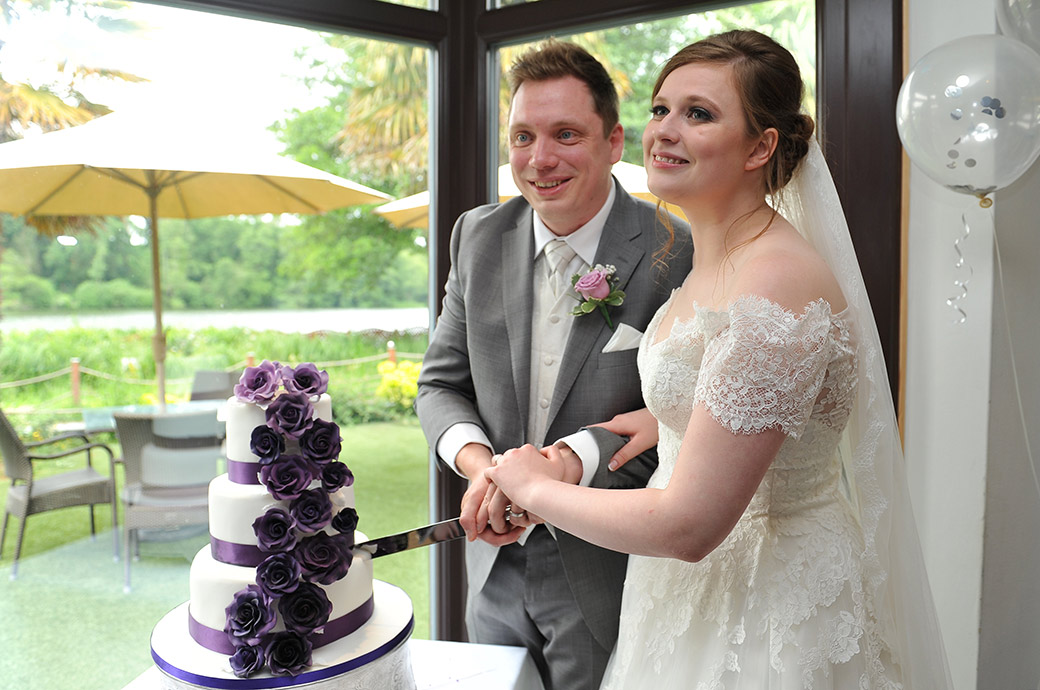 Bride and groom about to cut their cake captured at the start of the wedding breakfast at Surrey wedding venue Frensham Ponds Hotel in Farnham