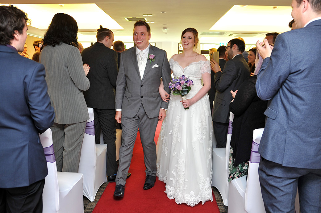 Happy overjoyed newlyweds at Surrey wedding venue Frensham Ponds Hotel walking down the aisle of the marriage ceremony room as husband and wife