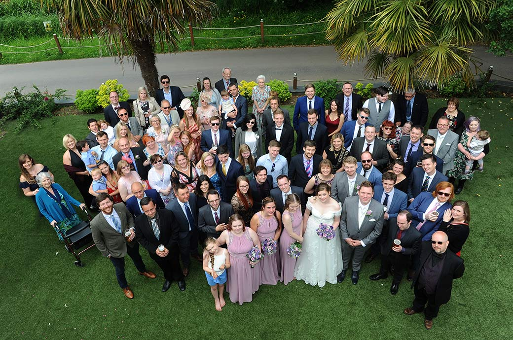 The classic everyone at the wedding picture captured from the balcony at the front of the distinctive Surrey venue Frensham Ponds Hotel