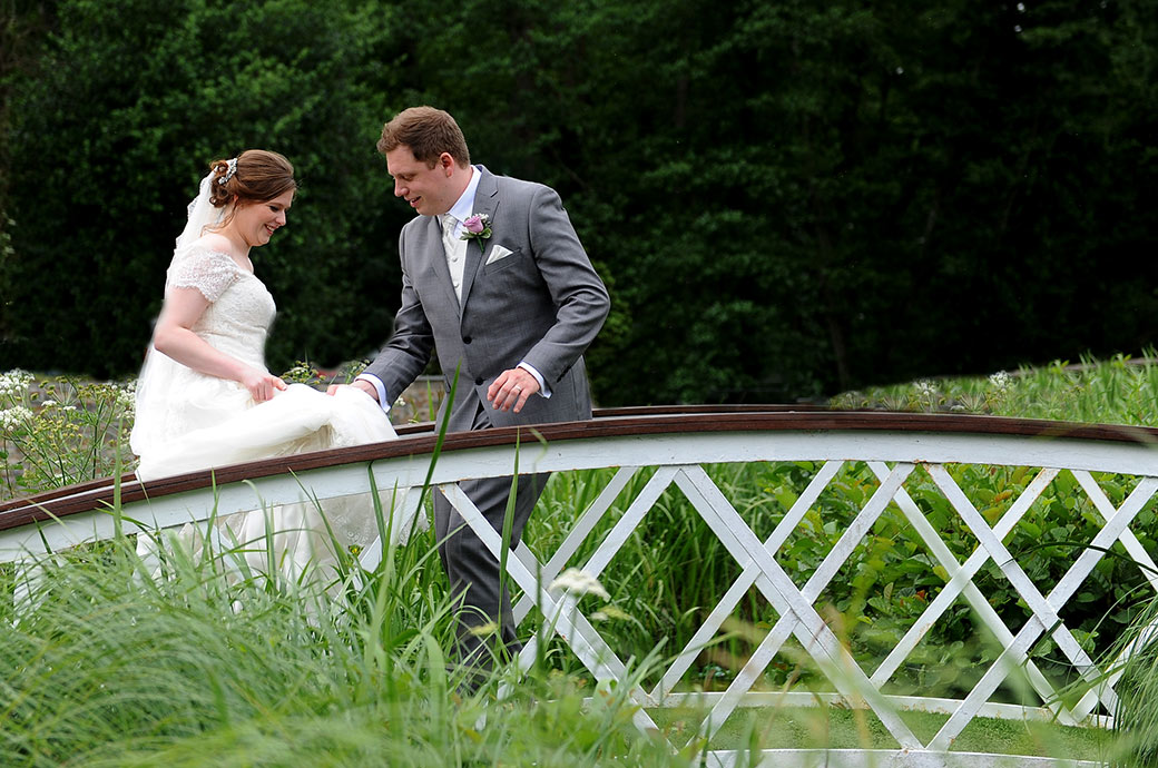 Groom helps Bride with her wedding dress as they walk over the cute little bridge from the boardwalk to the Frensham Ponds Hotel in Farnham Surrey