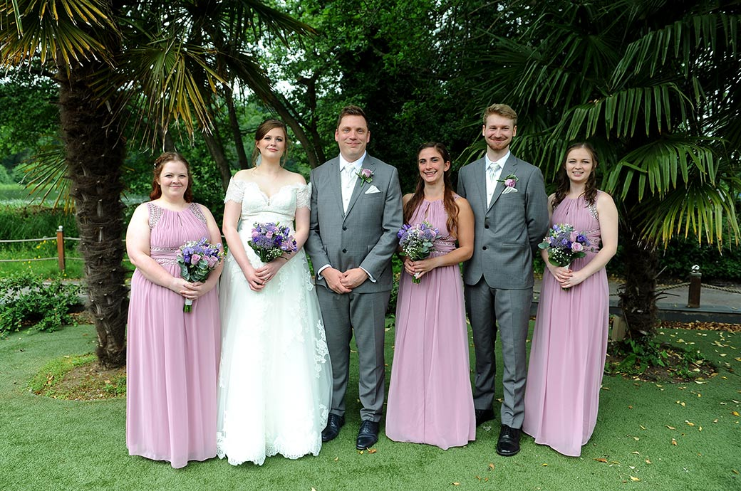 Relaxed group wedding photograph taken at Frensham Ponds Hotel  Surrey of a newlywed couple with their Bridesmaids and Best man