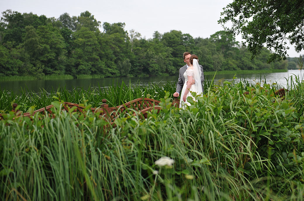 A wedding picture taken through the reeds of a newlywed couple kissing on the boardwalk opposite Surrey event venue the Frensham Ponds Hotel