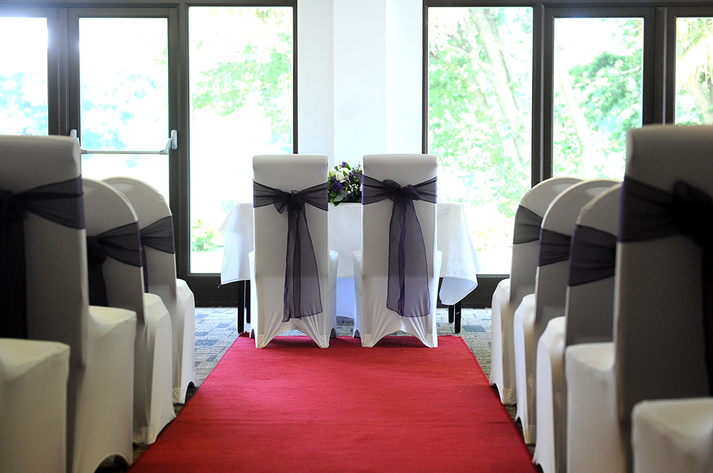 A view down the red carpeted aisle of the marriage ceremony room at Surrey wedding venue Frensham pond Hotel Farnham dressed ready for the arrival of guests