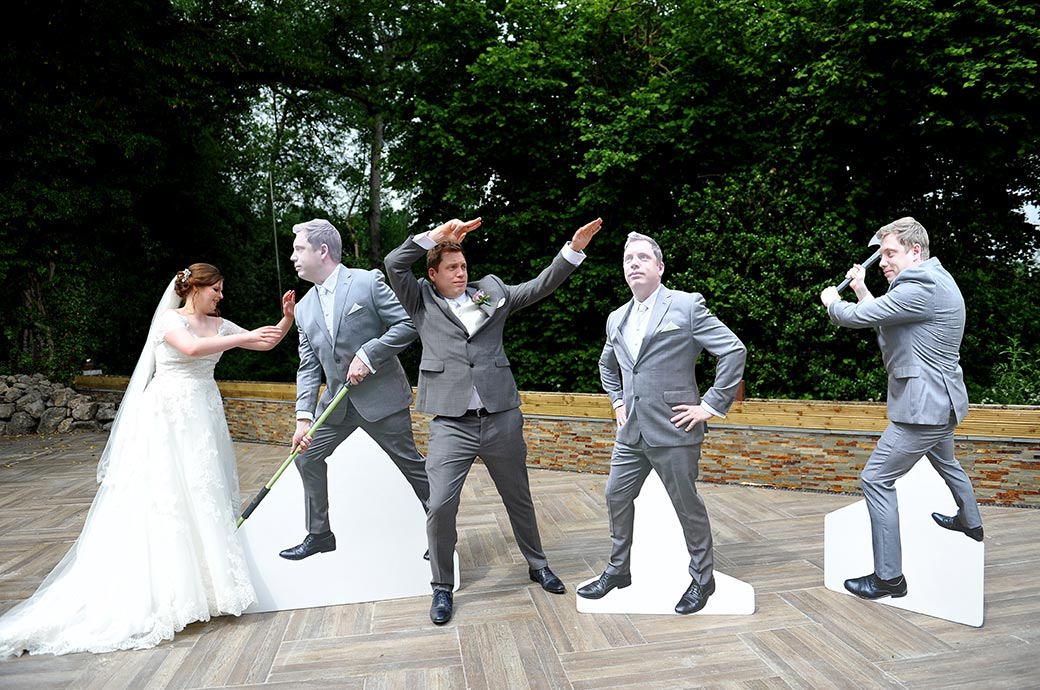 Unusual and fun wedding picture of the Bride and Groom at Surrey wedding venue Frensham Ponds Hotel posing with cardboard cut outs of the Groom