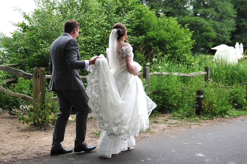 Groom helps to lift up the Bride's wedding dress as they walk along the road along the waterside back to the Frensham Ponds Hotel in Farnham Surrey