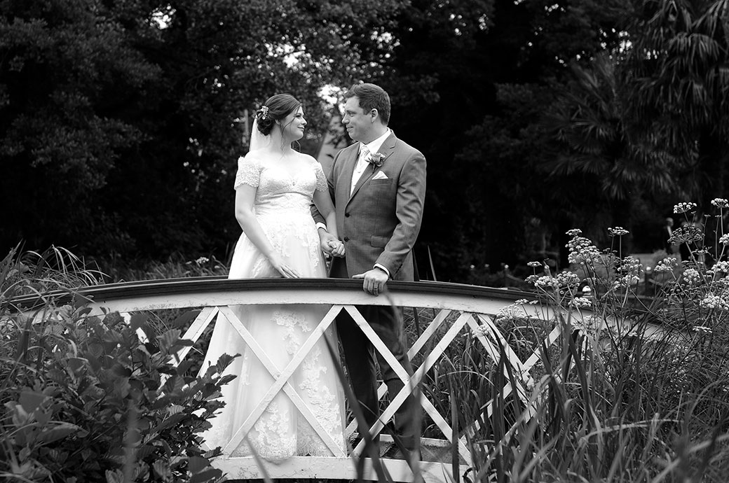 Loving newlywed couple at Surrey wedding venue Frensham Ponds Hotel hold hands and look into each others eyes as they stand on the ornamental bridge