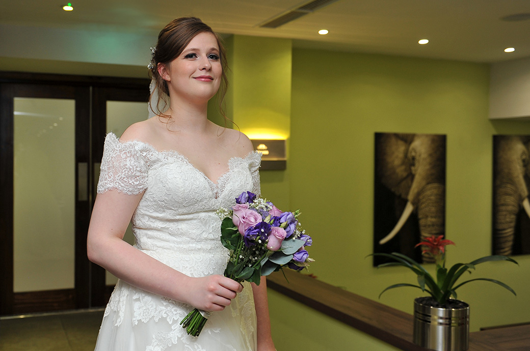 Radiant Bride walking with her bouquet past the reception at Frensham Ponds Hotel Surrey wedding venue on route for the marriage ceremony room