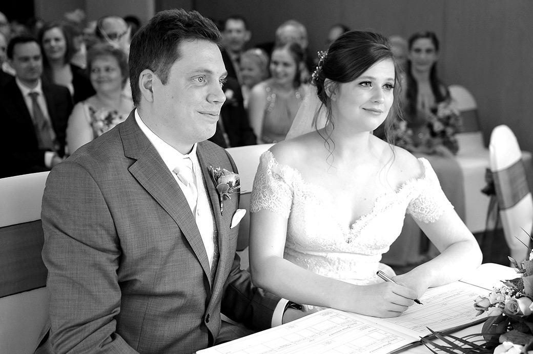 Excited and happy Bride and groom at the scenic Surrey wedding venue Frensham Ponds Hotel signing the marriage register