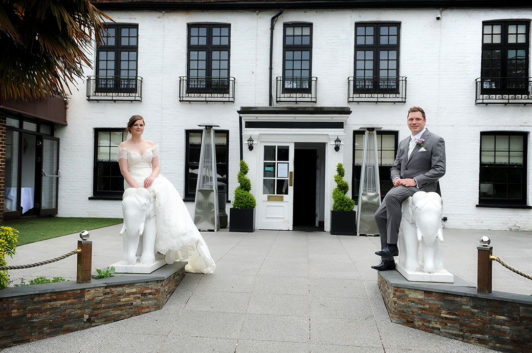 Bride and  Groom pose for a fun wedding picture sitting on a stone elephant at the front entrance to Frensham Ponds Hotel in Farnham Surrey