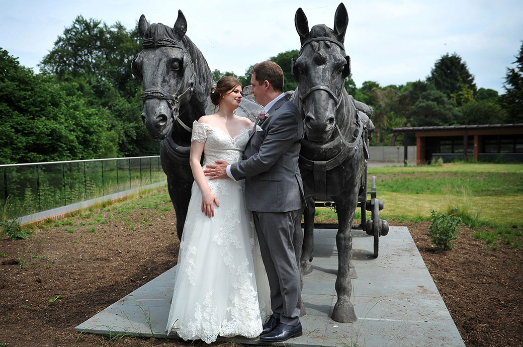 Bride and groom share a romantic moment in-between two impressive life-size horses and cart statues found at the front of the Frensham Ponds Hotel Surrey wedding venue