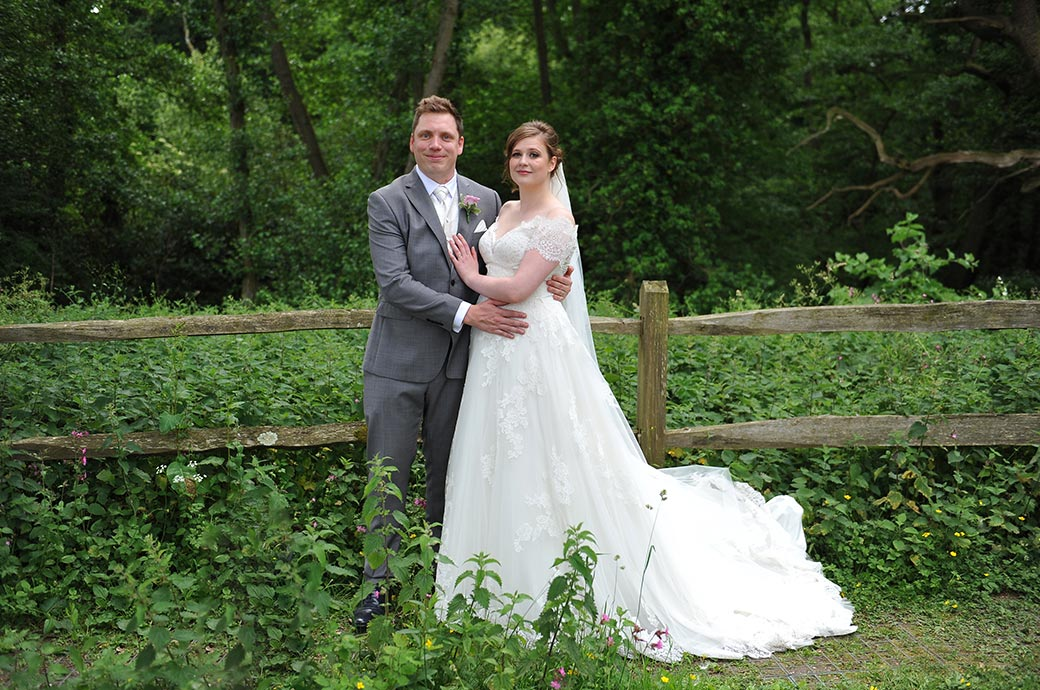 Bride and groom after their Frensham Ponds Hotel  marriage in Farnham Surrey pose for a wedding photograph by the side of a verdant country lane