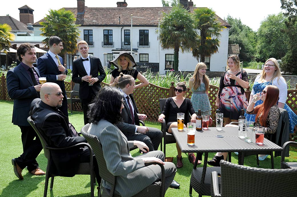 Wedding guests sitting out in the sun on the boardwalk with their drinks before the start of the marriage ceremony at the beautifully situated Frensham Ponds Hotel in Surrey