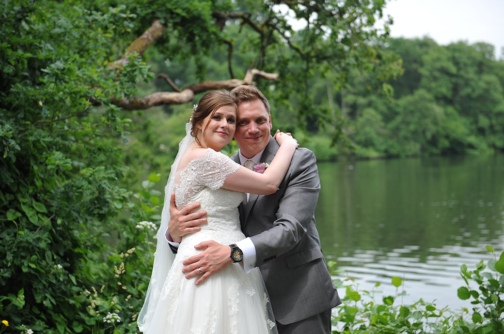 Happy and relaxed Bride and groom at Surrey wedding venue Frensham Ponds Hotel have a hug after a romantic walk down the lane and alongside the large pond