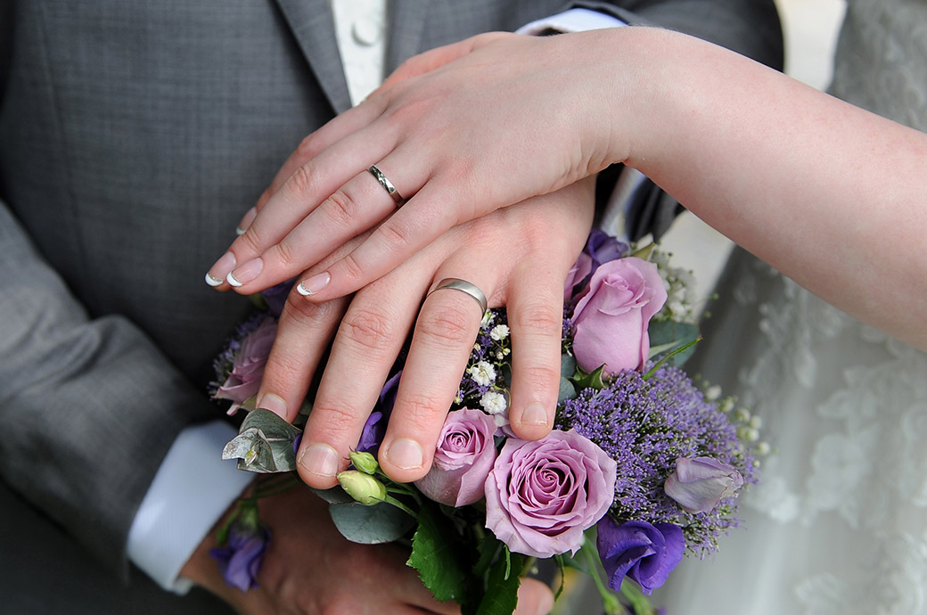 Newlyweds captured at Frensham Ponds Hotel in Surrey as they show off their wedding rings with a colourful bouquet background