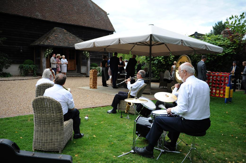 Wedding picture of a five piece band playing some upbeat tunes as the wedding guests arrive in the garden for drinks at Gate Street Barn in Bramley Guildford Surrey